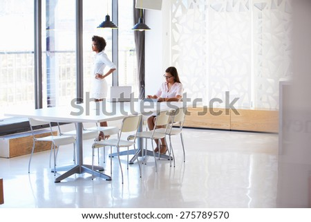 Two women working with digital tablet in empty meeting room - stock photo