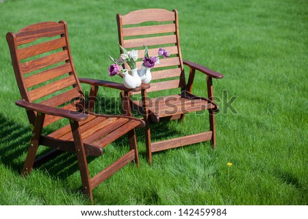 Two wood chairs on the grass with vase of flowers on them - stock photo
