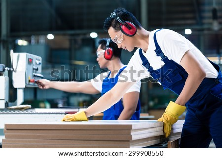Two wood workers in carpentry cutting boards putting them in saw - stock photo