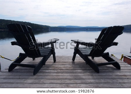 Two wooden adirondack chairs on a boat dock on a beautiful lake in the evening - stock photo