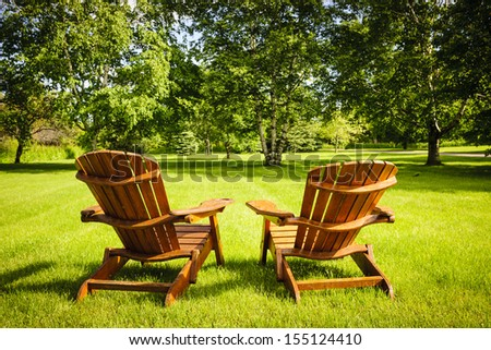 Two wooden adirondack chairs on lush green lawn with trees - stock photo