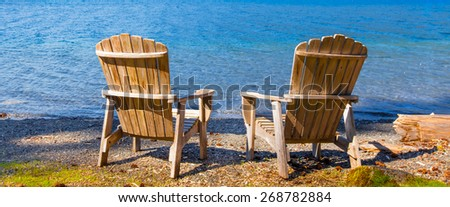 two wooden adirondack chairs on the shore of a lake facing the water viewed from