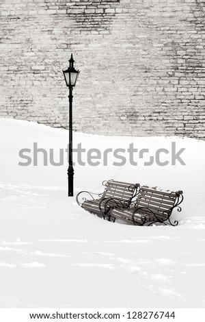 Two wooden and metal park benches in deep white snow near street lantern at winter. Limestone wall in the background. - stock photo