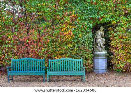 Two wooden benches on alley in front of bushes with lush colorful foliage and old sculpture in autumn Racconigi park, Italy. - stock photo