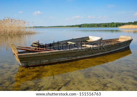 Two wooden boats are on the shoal of the forest lake.