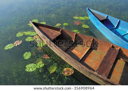 two wooden boats docked on Plav Lake, Montenegro - stock photo