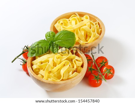 two wooden bowls with fresh pasta and tomatoes