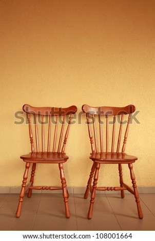 Two wooden chair next to yellow wall