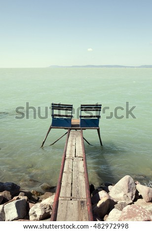 Two wooden chairs on a wooden pier at Lake Balaton, Hungary, with instragram style filter