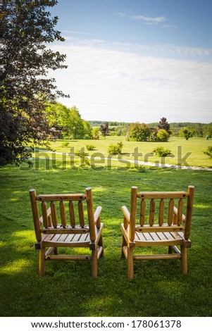 Two wooden chairs on lush green lawn with view of countryside in summer - stock photo