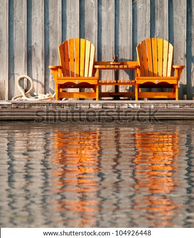 Two wooden chairs reflected in the water - stock photo