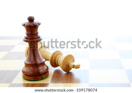 Two wooden chess pieces alone on a chess board. - stock photo