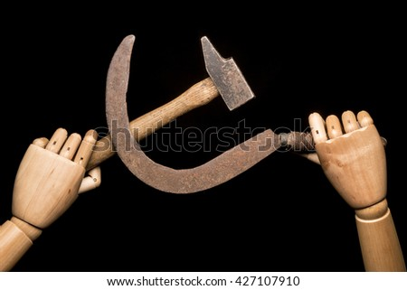 Two wooden hands brandishing a rusty sickle and a used hammer. On black background. With copy-space. - stock photo