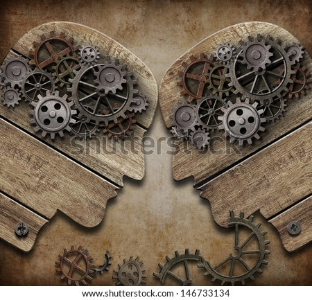 two wooden heads with gears coming into collision concept - stock photo