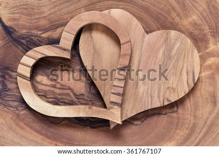two wooden hearts on a wooden background, olive wood, copyspace, horicontal, concept wedding