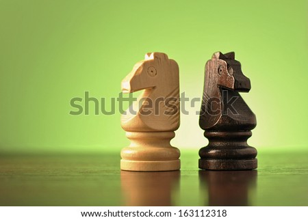 Two wooden knight chess pieces in opposing light and dark colours standing back to back on a reflective wooden surface against green with copyspace - stock photo