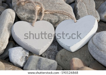 two wooden love hearts on the rocks of a beach - stock photo