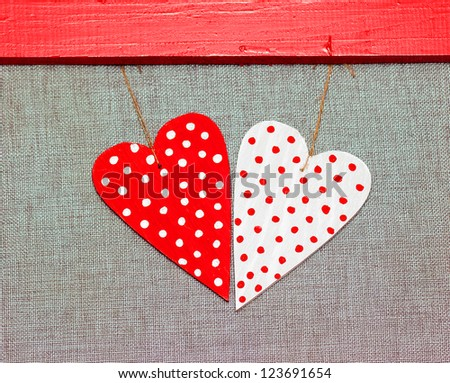 two wooden multicolored hearts in the red frame on grey background