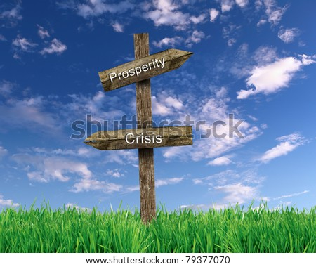 two wooden roadsigns with words prosperity and crisis on them against blue sky - stock photo