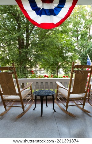 Two Wooden Rocking Chairs with Small Table at the Terrace with Conceptual American Flag Fronting Tall Green Trees at the Garden - stock photo