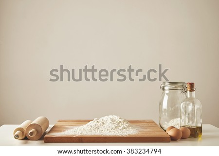 Two wooden rolling pins, extra virgin olive oil, transparent jar and wooden cutting board with white flour, chiken eggs isolated. Everything prepared for dough making - stock photo