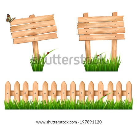 Two wooden signs and a fence with grass.  - stock photo