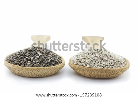 two wooden spoons with black and white chia seeds isolated on white - stock photo