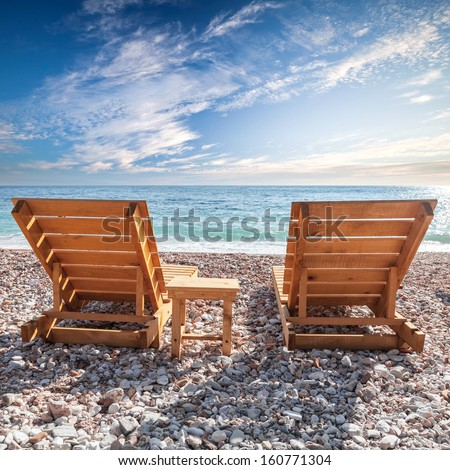 Two wooden sun loungers stand on the Adriatic Sea coast under dramatic cloudy sky
