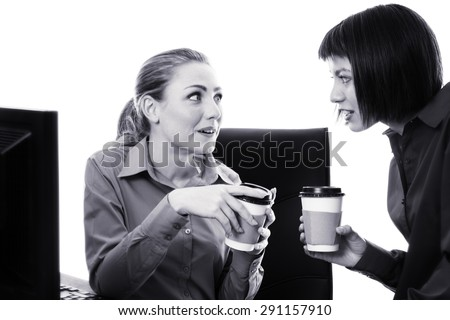 two work colleagues Having a chat and gossip at work over a coffee