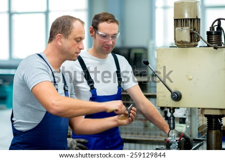 two worker in factory on the machine - stock photo
