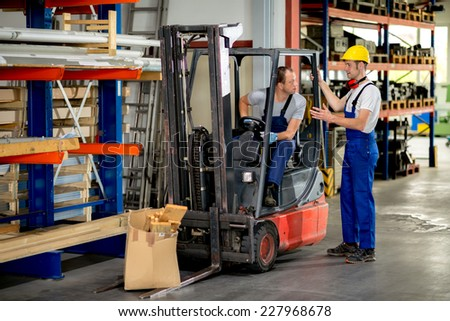 two worker with pallet transporter in factory - stock photo