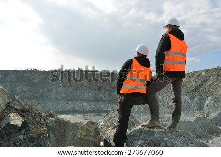 Two workers and quarry in background - stock photo