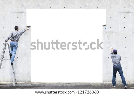 two workers are painting blank area on the wall - stock photo