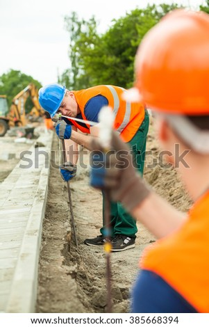 Two workers checking distance at construction site - stock photo