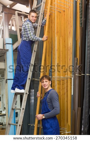 Two workers choosing PVC window  frames at stand - stock photo