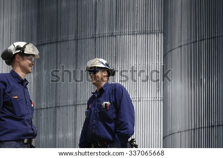 two workers, engineers and stainless-steel wall - stock photo
