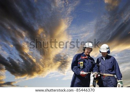 two workers, engineers, walking under a cloudy sunset sky, leaving work conceptual. - stock photo