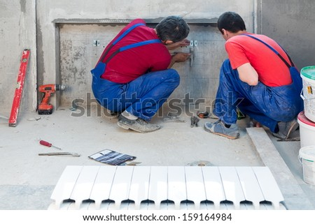 Two workers have made fastening in a niche for radiators in apartment with a rough finish - stock photo