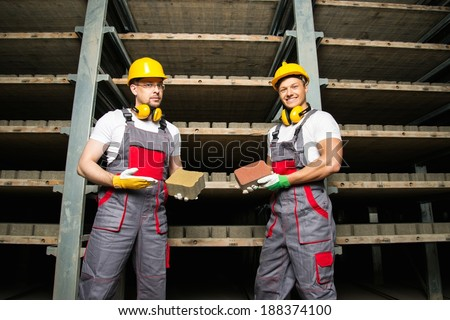Two workers in a storage room on a factory holding their product - stock photo