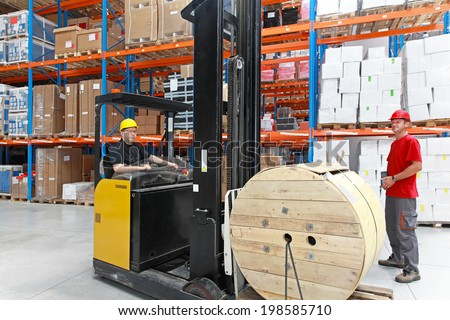 Two workers in distribution warehouse with forklift - stock photo