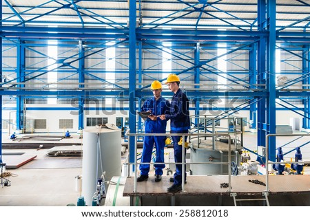 Two workers in large metal workshop or factory checking work standing on large machine - stock photo