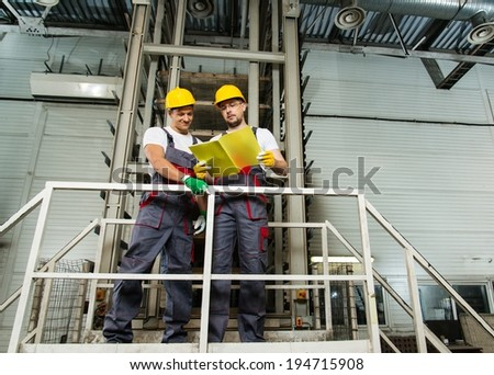 Two workers in safety hats on a factory reading plan  - stock photo