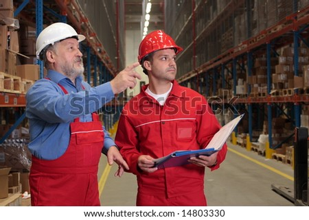 two workers in uniforms in warehouse - stock photo