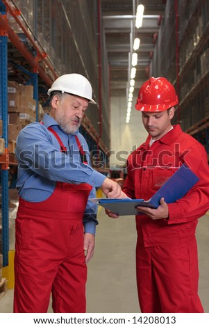 two workers in uniforms in warehouse reading report