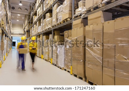 Two workers in warehouse controlling products - stock photo