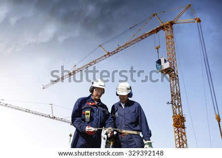 two workers inside building-site, cranes and scaffolding - stock photo