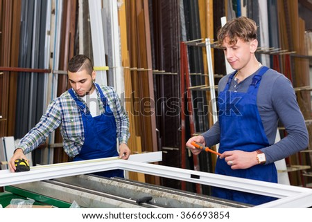 Two workers inspecting PVC window profile at stand. Focus on left man - stock photo