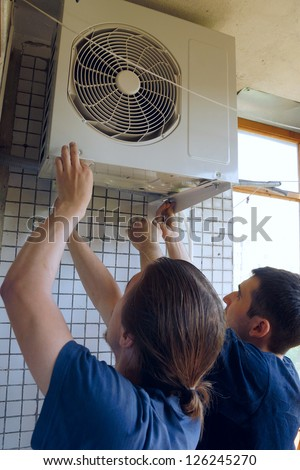 Two workers install air conditioning - stock photo