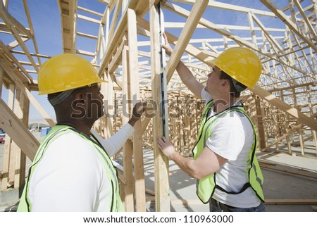 Two workers measuring at construction site - stock photo