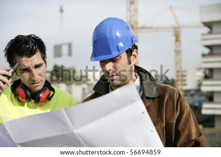 Two workers reading a plan